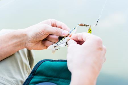 hoof: Angler fixing lure at hoof of fishing rod