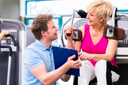 trainers: Trainer in sport gym assisting senior woman exercising on resistance machine, showing her the training schedule
