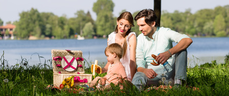 Family having picnic at lake sitting on meadow eating and drinking