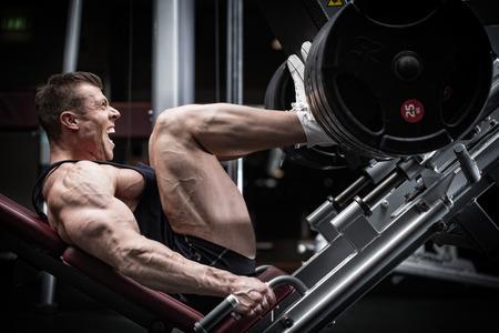pesas: Hombre en el entrenamiento de gimnasia en prensa de piernas para definir sus m�sculos superiores de la pierna Foto de archivo