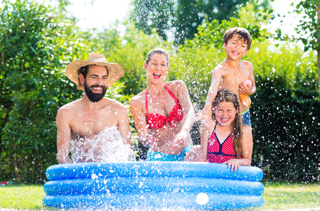 Family in garden pool cooling down by splashing water