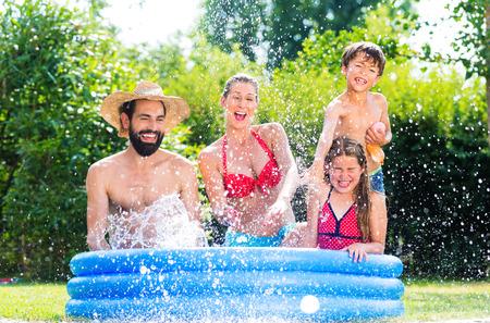 Familie in de tuin van het zwembad af te koelen door opspattend water