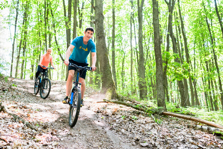downhill: Couple, man and woman, on mountain bike bicycle going downhill