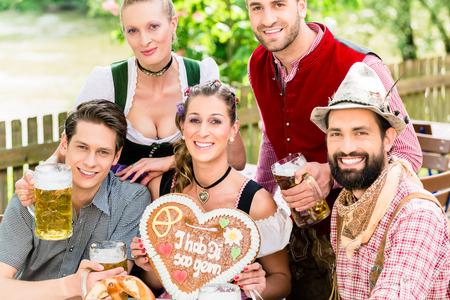 tracht: people with gingerbread heart in beer garden drinking beer in summer Stock Photo