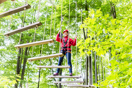 rope: Teenage girl, walking on rope bridge in climbing course enjoying the trill of the sport Stock Photo