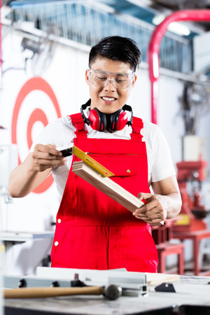 safety at work: Asian Carpenter measuring piece of wood standing in factory or workshop Stock Photo