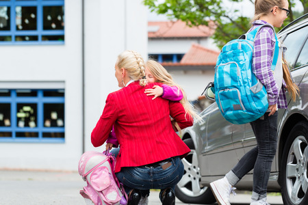 day of school: Mother hugging child after bringing her to school