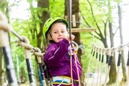 aventura: Escalada Chica en curso alto cuerda disfrutando de la aventura Foto de archivo