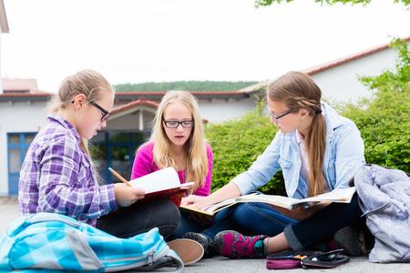 grupos de personas: Los estudiantes que hacen la preparación para la escuela juntos la lectura en sus libros