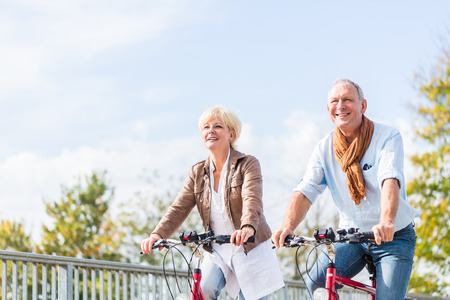 leisure time: Senior couple, married woman and man, riding their bicycles over a bridge enjoying some leisure time Stock Photo