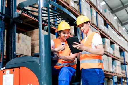 carretillas almacen: Los trabajadores de almacén logístico en la lista de comprobación de la carretilla elevadora