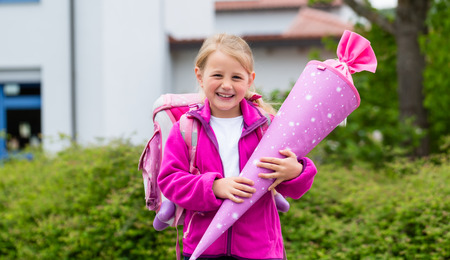 day of school: Student at first day in school with traditional candy cone