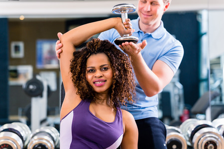 trainers: African woman and trainer exercising in gym for better fitness Stock Photo