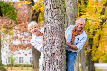 hide and seek: Couple, senior man and woman, flirting with each other playing hide and seek around a tree in fall tree Stock Photo