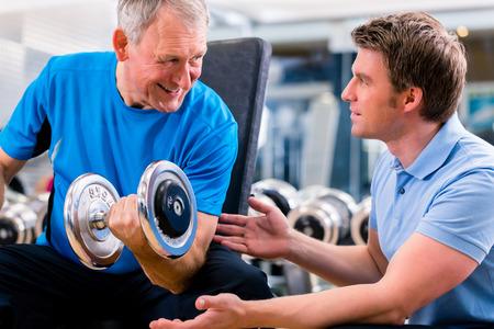 levantando pesas: Hombre mayor y entrenador en el ejercicio en el gimnasio con pesas con mancuernas Foto de archivo