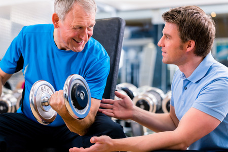 man lifting weights: Senior man and trainer at exercise in gym with dumbbell weights