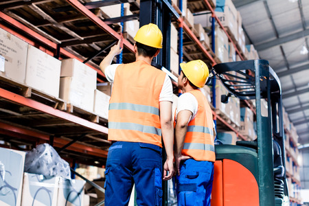 inventories: Worker team taking inventory in logistics warehouse