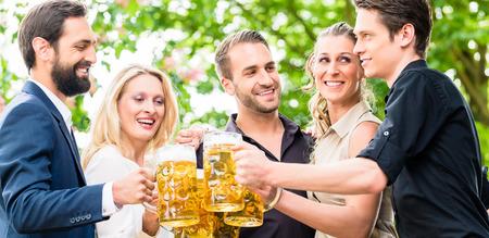 after to work: Los amigos o colegas en el jard�n de la cerveza despu�s del trabajo brindando con bebidas