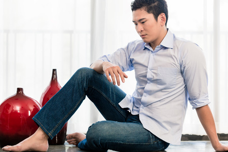 lonelyness: Depressed Asian man sitting on apartment floor Stock Photo