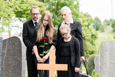mourn: Family mourning at grave on graveyard or cemetery