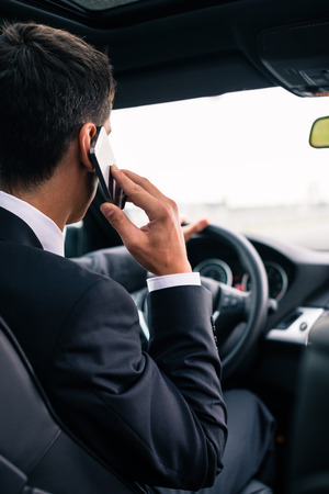 men in suit: Man using his phone while driving the car Stock Photo