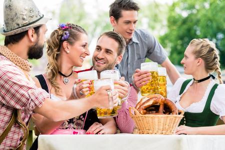 tracht: Friends in Bavarian beer garden drinking in summer