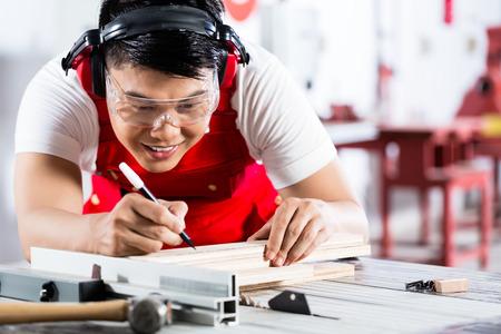 Aziatische Chinese Carpenter snijden hout met cirkelzaag in zijn atelier Stockfoto
