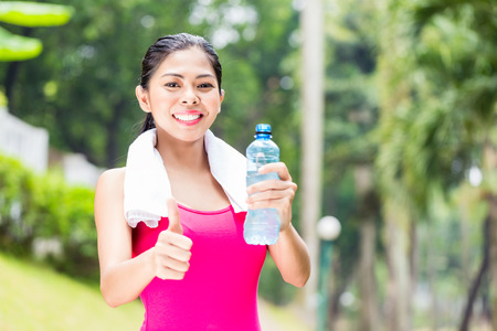 replenishing: Asian woman having successful sport training giving thumbs up with water bottle in her hands