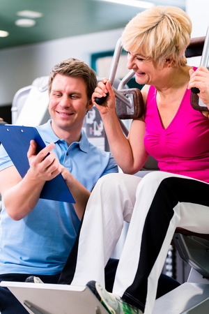fitness center: Trainer in sport gym assisting senior woman exercising on resistance machine, showing her the training schedule