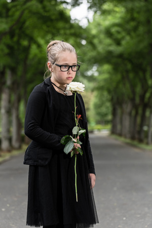 deceased: Girl with white rose mourning deceased on graveyard being an orphan now