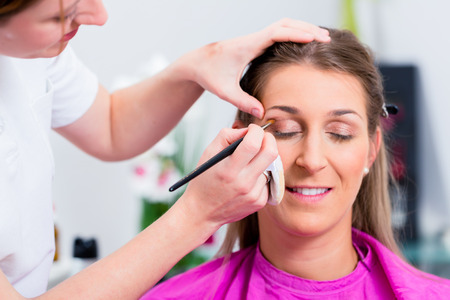 eye service: Woman with beautician in cosmetic salon receiving makeup