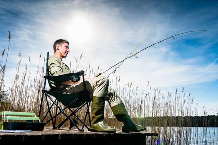 Man vissen op het meer zitten op de steiger dicht bij het water
