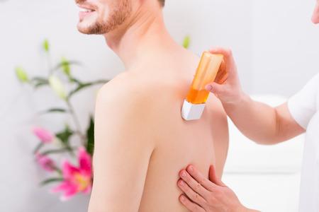 depilacion con cera: El hombre que recibe la depilaci�n para la depilaci�n en sal�n de belleza Foto de archivo