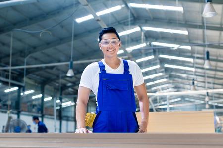 ワーク ショップでカメラを見て木の板で立っているアジアの大工
