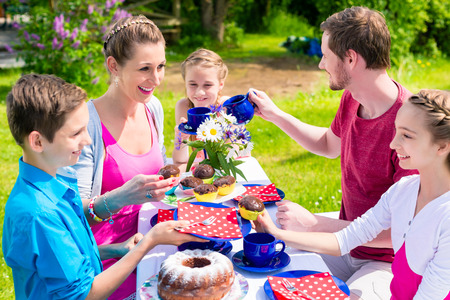 coffee and cake: Family having coffee and cake in garden in front of their home at a table outdoors Stock Photo