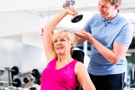 aide à la personne: Senior femme à l'exercice de sport avec des haltères dans le gymnase avec un entraîneur à gagner en force et conditionnement physique