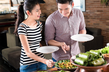 indonesian food: Asian woman and man choosing food at Indonesian buffet in restaurant