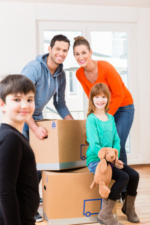 family moving house: Family with moving boxes in new home or house looking around