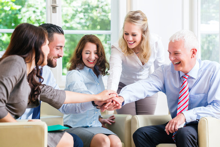 trust people: Team of business people celebrating success stacking hands together Stock Photo