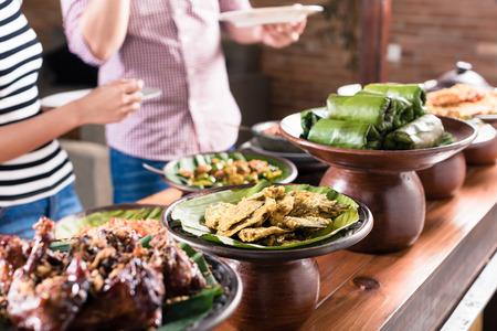 Asiatische Frau und Mann, die Wahl Essen im indonesischen Stücksbuffet im Restaurant