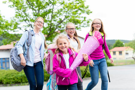 day of school: Group of students going back to school running on the schoolyard Stock Photo