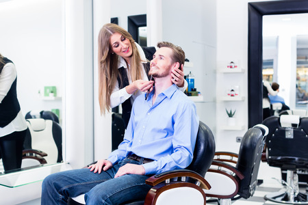 barber: Man being shaved by barber woman