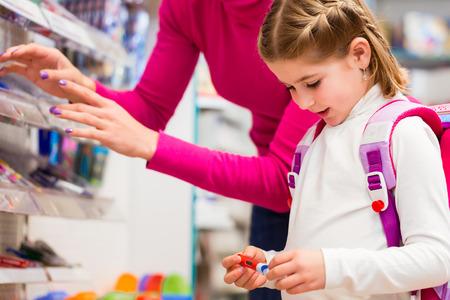 Familie Kaufschulmaterial in Schreibwarenladen, kleines Mädchen schaut auf einen Füllfederhalter Lizenzfreie Bilder