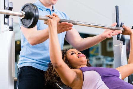 aide à la personne: femme noire avec un entraîneur de poids de levage sur les haltères dans le gymnase pour le fitness