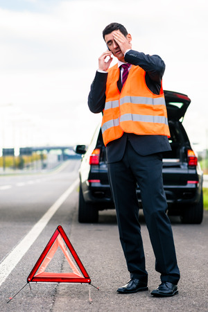 safety vest: Man with car breakdown erecting warning triangle on road