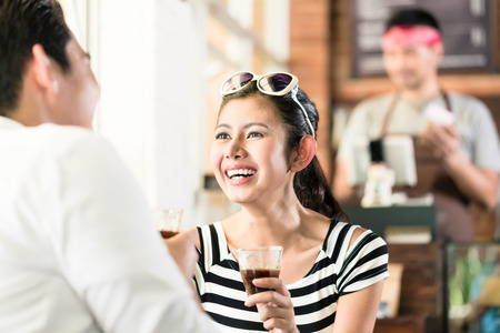 woman shop: Asian couple, Indonesian woman and Korean man, in cafe flirting while drinking coffee, barista in the background Stock Photo