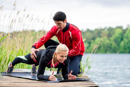 Frau mit persönlichem Trainer, die Eignung tut Push-up-
