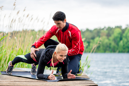 outdoor activities: Woman with personal trainer doing fitness push-up
