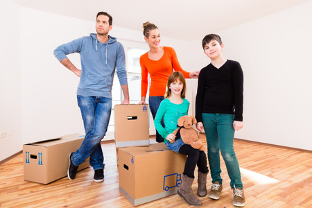 move in: Family with moving boxes in new home or house looking around