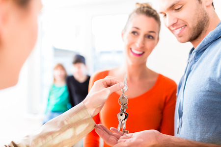 moving out: Accommodation broker giving home key to family Stock Photo
